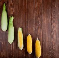 gekookte en ongekookte maïskolven aan de linkerkant en houten achtergrond met exemplaarruimte foto