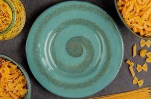 bovenaanzicht van verschillende soorten macaroni in pot en kommen rond plaat op grijze doek achtergrond foto