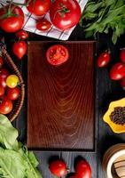 bovenaanzicht van groenten als tomaat groene muntblaadjes spinazie en gesneden tomaat in lade op houten achtergrond foto