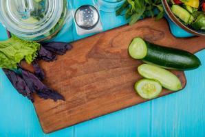 bovenaanzicht van gesneden en gesneden komkommer op snijplank met basilicum sla munt groentesalade detox water en zout op blauwe achtergrond