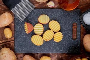 bovenaanzicht van gegolfde plakjes aardappelen op snijplank met hele kruidenboter en zout rond op houten achtergrond