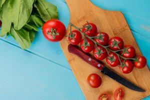 bovenaanzicht van tomaten met mes op snijplank en spinazie op blauwe achtergrond