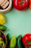 bovenaanzicht van groenten als tomaat komkommer peper met citroen en zwarte peper in knoflook crusher op groene achtergrond met kopie ruimte foto