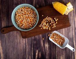 bovenaanzicht van kom maïs zaden gesneden maïs op snijplank met lepel vol maïs zaden op houten achtergrond