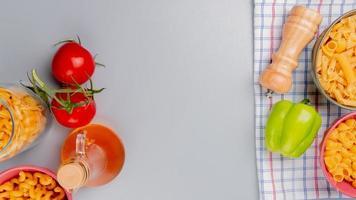bovenaanzicht van verschillende soorten macaroni als cavatappi pipe-rigate en anderen met tomatenboter peperzout op geruite doek en blauwe achtergrond met kopie ruimte