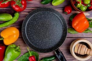 bovenaanzicht van groenten als tomaat komkommer peper met bladeren en zwarte peper in knoflook crusher en koekenpan op houten achtergrond