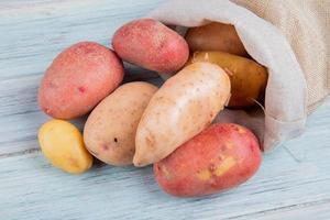 bovenaanzicht van roodbruine nieuwe en rode aardappelen morsen uit zak op houten achtergrond foto