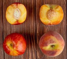 bovenaanzicht van patroon van hele en half gesneden perziken op houten achtergrond foto