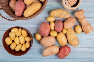 bovenaanzicht van nieuwe aardappelen in kom en anderen van verschillende soorten in mand met knoflook crusher zout en andere aardappelen op houten achtergrond foto