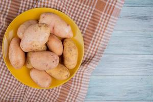 bovenaanzicht van witte en gele aardappelen in plaat op geruite doek en houten achtergrond met kopie ruimte