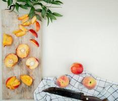 bovenaanzicht van gesneden en gesneden perziken op snijplank met hele perziken en mes op doek op witte achtergrond versierd met bladeren met kopie ruimte