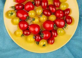 bovenaanzicht van tomaten in plaat op blauwe doek achtergrond foto