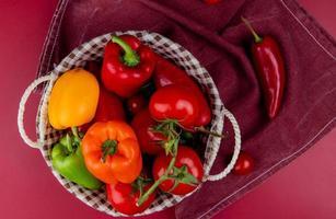 bovenaanzicht van groenten als peper, tomaat, komkommer in mand op bordo-doek en bordo-achtergrond