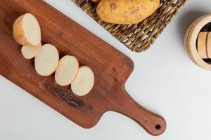 bovenaanzicht van gesneden en gesneden aardappel op snijplank met geheel in plaat en zwarte peper op witte achtergrond