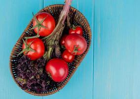 bovenaanzicht van groenten als basilicum en tomaat in mand op blauwe achtergrond met kopie ruimte