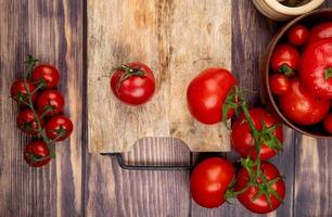 bovenaanzicht van tomaten op snijplank met andere op houten achtergrond