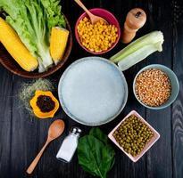Bovenaanzicht van gekookte likdoorns maïs zaden lege plaat sla met maïsschelp en zijde zwarte peper groene erwten zout lepel spinazie op zwarte achtergrond