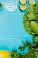 bovenaanzicht van groenten als komkommersla, koriander met detoxwater en citroen op blauwe achtergrond