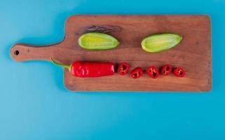 bovenaanzicht van gesneden en gesneden groenten als peper en komkommer op snijplank en blauwe achtergrond met kopie ruimte foto