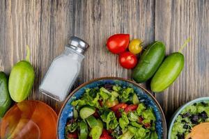 bovenaanzicht van groentesalades met tomaten komkommer gesmolten olie en zout op houten achtergrond foto