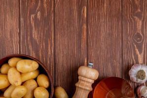 bovenaanzicht van aardappelen in kom met knoflookzout en boter op houten achtergrond met kopie ruimte foto