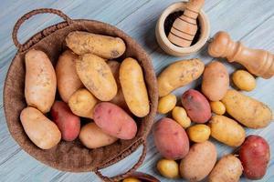 bovenaanzicht van aardappelen in mand met zwarte peper zaden zout en andere aardappelen op houten achtergrond foto