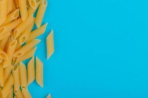bovenaanzicht van penne pasta aan de linkerkant en blauwe achtergrond met kopie ruimte