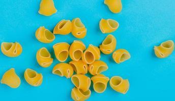 bovenaanzicht van pipet-rigate pasta op blauwe achtergrond foto