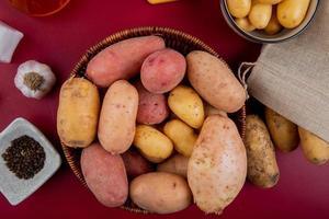 bovenaanzicht van aardappelen in mand met knoflook zwarte peper zaden zout op bordo achtergrond foto