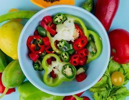 bovenaanzicht van peper plakjes in kom met groenten als tomaat paprika sla met citroen op blauwe achtergrond