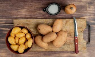 bovenaanzicht van aardappelen in kom en op snijplank met mes en zout op houten achtergrond foto