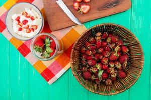 bovenaanzicht van aardbeien in mand met kommen kwark en aardbeien op doek op groene achtergrond foto