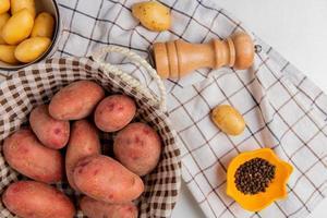 bovenaanzicht van aardappelen in mand en in kom met zout zwarte peper op geruite doek op witte achtergrond foto