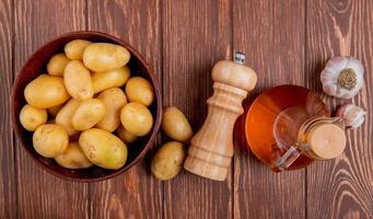 bovenaanzicht van aardappelen in kom met knoflookzout en boter op houten achtergrond