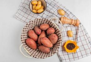 bovenaanzicht van aardappelen in mand en kom met zout zwarte peper op doek op witte achtergrond