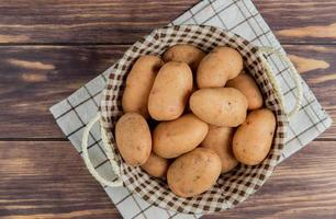 bovenaanzicht van aardappelen in mand op geruite doek en houten achtergrond