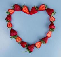 bovenaanzicht van aardbeien op blauwe achtergrond met kopie ruimte hart concept foto