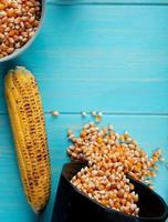 bovenaanzicht van maïskolf en maïs zaden morsen uit pot op blauwe achtergrond