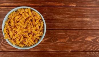 bovenaanzicht van rotini pasta in kom op houten achtergrond met kopie ruimte foto