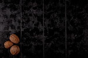 bovenaanzicht van hele walnoten op een zwarte houten achtergrond foto
