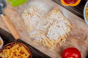 bovenaanzicht van tagliatelle macaroni met bloem peper en tomaat op snijplank met andere soorten ketchup op houten achtergrond