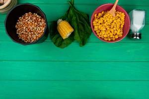bovenaanzicht van maïs zaden met gesneden maïs zout en spinazie op groene achtergrond met kopie ruimte foto