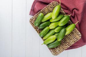 bovenaanzicht van komkommers in mandplaat op bordodoek aan rechterkant en houten achtergrond met exemplaarruimte foto
