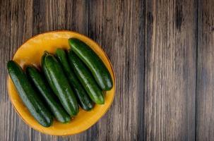komkommers op een gele plaat op houten achtergrond met kopie ruimte foto