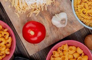 bovenaanzicht van tagliatelle macaroni met bloem, knoflook en tomaat op snijplank met andere soorten pasta op houten achtergrond