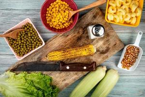 bovenaanzicht van maïskolf en mes op snijplank met groene erwten maïs zaden sla zout op houten achtergrond