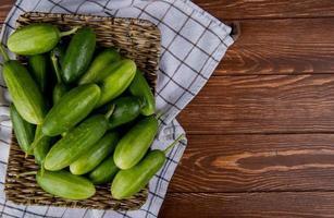 bovenaanzicht van komkommers in mand plaat op geruite doek en houten achtergrond met kopie ruimte