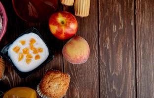bovenaanzicht van kwark met perziken cupcakes op houten achtergrond met kopie ruimte