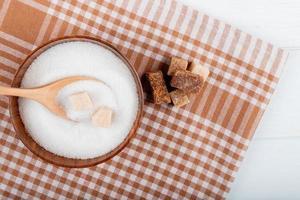 Bovenaanzicht van witte suiker in een houten kom met een lepel en suikerklontjes en stukjes palmsuiker op geruit tafelkleed met kopie ruimte