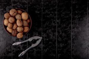 bovenaanzicht van hele walnoten in een houten kom op zwarte achtergrond met kopie ruimte
